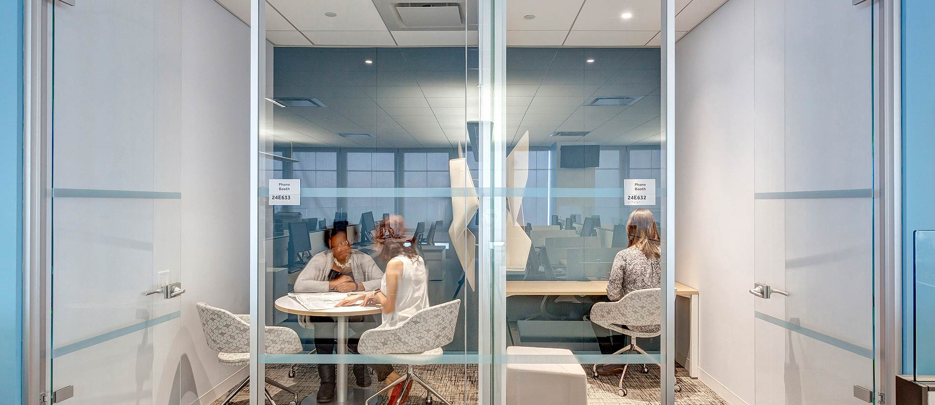 SILENCE partition walls and glass pane vertical surfaces creating a divider between three employees