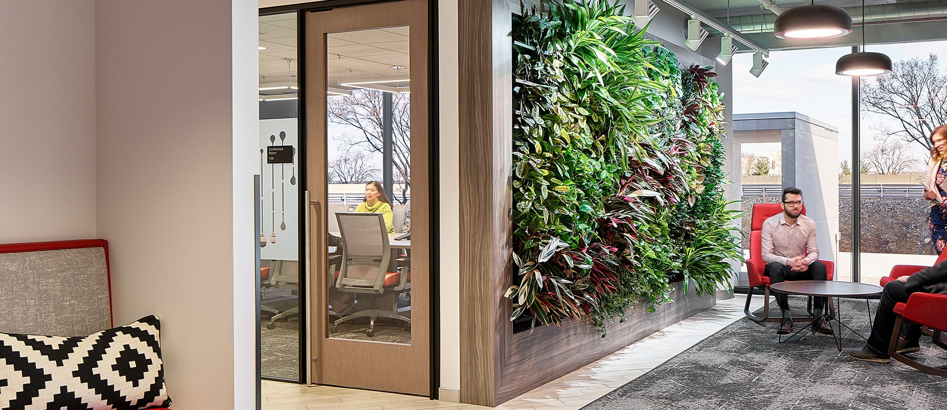 Green wall separates a conference and waiting room designed with One LP glass door panel