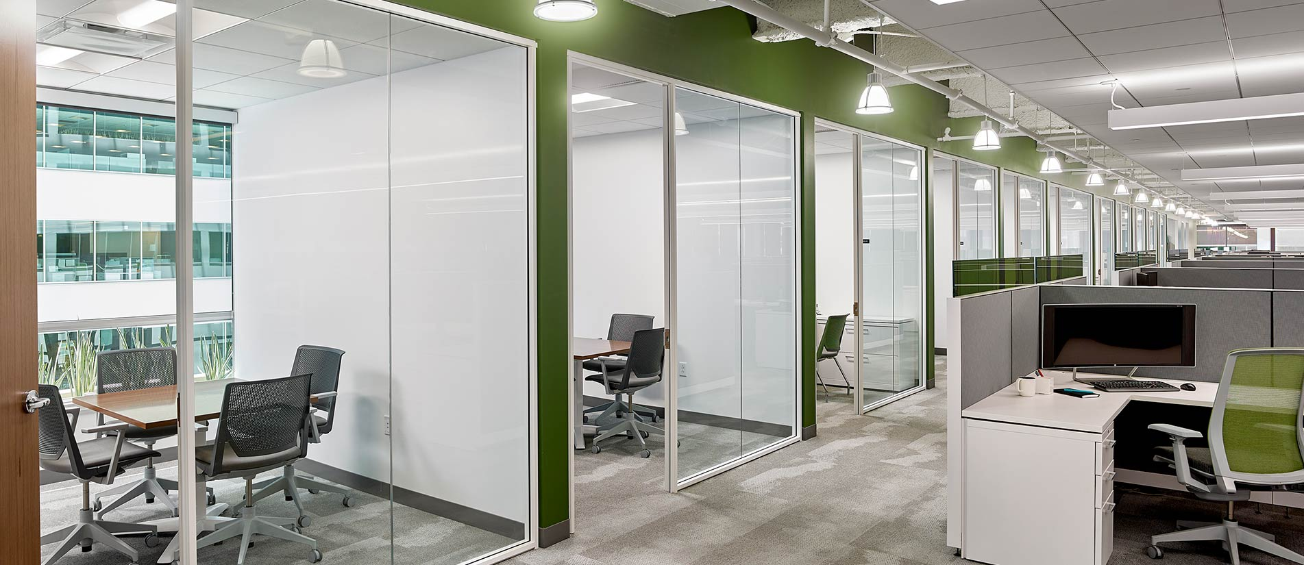 One LP glass office wall system creates meeting rooms divided by glass doors and partition walls